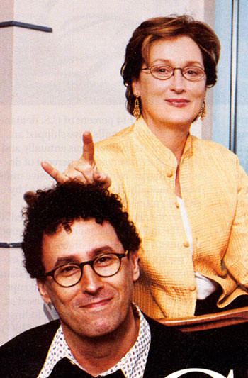 "Actress Meryl Streep gives the sign of the Devil just over the head of ""Angels in America"" director, Mike Nichols."